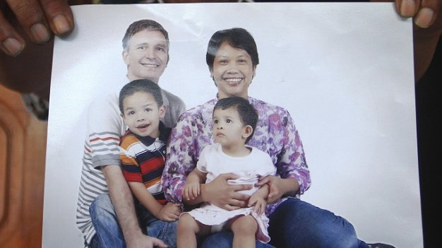 Widi Yuwono, the brother of Yuli Hastini, right, shows her sister's family portrait with her Dutch husband John Paulissen and their two children Arjuna and Sri who were on board of the crashed Malaysia Airlines flight 17, at his residence in Solo, Central Java, Indonesia, Friday, July 18, 2014. The Malaysian jetliner that went down in war-torn Ukraine did not make any distress call, Malaysian Prime Minister Najib Razak said Friday, adding that its flight route had been declared safe by the global civil aviation body. (AP Photo)