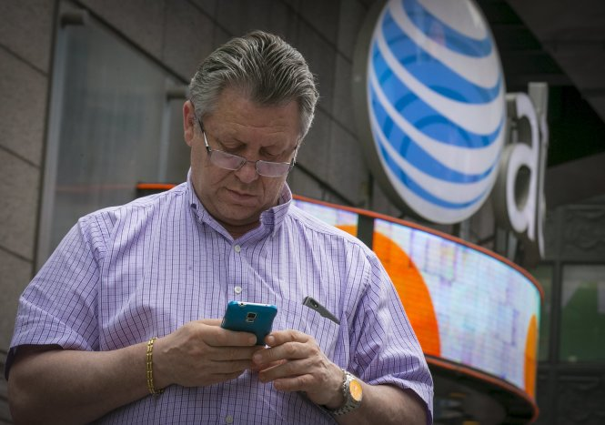 A man uses his phone outside the AT&T store in New York's Times Square, June 17, 2015. The U.S. Federal Communications Commission on Wednesday proposed a $100 million fine for AT&T Inc, accusing the No. 2 wireless carrier of misleading customers who paid for unlimited data plans about possible slowing of download speeds. REUTERS/Brendan McDermid
