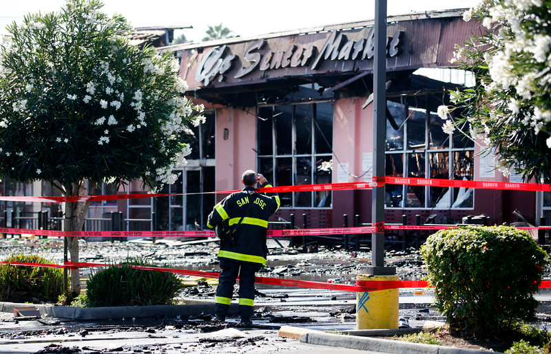 A firefighter takes a photograph of the the charred remains of the Cho Senter Market destroyed early Sunday morning Oct. 4, 2015, in a 4-alarm fire in San Jose, Calif. (Karl Mondon/Bay Area News Group)