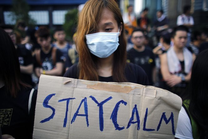 REFILE - CORRECTING TYPO A student hold a sign which reads 'Stay Calm' as protesters gather around the Golden Bauhinia Square before an official flag raising ceremony to commemorate the Chinese National Day in Hong Kong, October 1, 2014. Tens of thousands of pro-democracy protesters extended a blockade of Hong Kong streets on, stockpiling supplies and erecting makeshift barricades ahead of what some fear may be a push by police to clear the roads before Chinese National Day.  REUTERS/Carlos Barria (CHINA - Tags: CIVIL UNREST POLITICS)