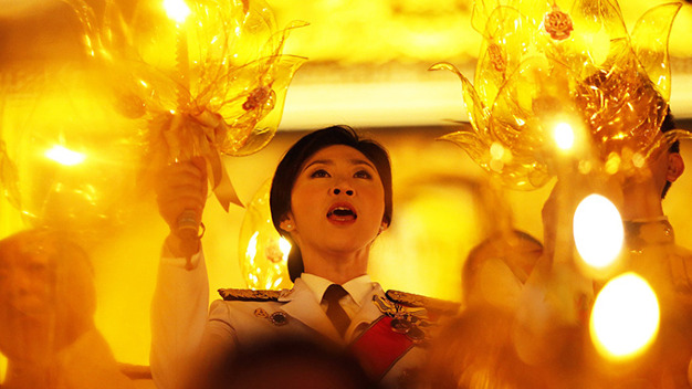 Thai Prime Minister Yingluck Shinawatra holds a candle and sings as she takes part in birthday celebrations for Thailand's revered King Bhumibol Adulyadej in Bangkok, in this December 5, 2013 file picture. To match Special Report THAILAND-POLITICS/ REUTERS/Damir Sagolj/Files (THAILAND - Tags: POLITICS ROYALS)