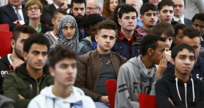 Migrants aged between 16 and 21 years, coming from different countries, attend a lesson on basics in law by Bavarian Justice Minister Winfried Bausback (unseen) at a trade school in Ansbach, Germany, January 11, 2016. REUTERS/Michaela Rehle