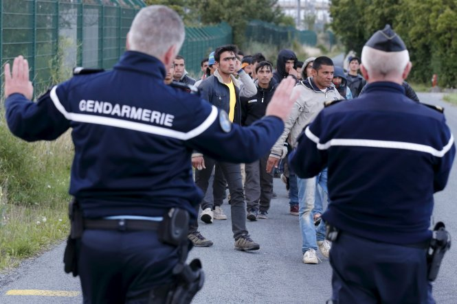 French gendarmes block migrants along a road to prevent them access to train tracks which lead to the Channel Tunnel in Frethun, near Calais, France, July 29, 2015. A migrant died trying to cross to Britain from France early on Wednesday, French police said, adding to a number of recent deaths in the Channel Tunnel as British ministers and security chiefs were to meet over the crisis in Calais. There were about 1,500 attempts by migrants to access the tunnel on Tuesday night, a Eurotunnel spokesman said, after 2,000 attempts the previous night. Picture taken july 29, 2015. REUTERS/Pascal Rossignol