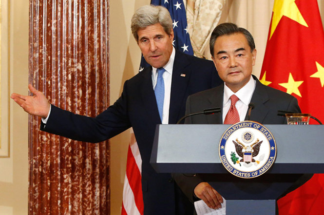 U.S. Secretary of State John Kerry (L) directs China's Foreign Minister Wang Yi to their exit following remarks to reporters before their meeting at the State Department in Washington October 1, 2014. Kerry on Wednesday called for Hong Kong to show restraint toward pro-democracy protesters, while Wang said countries should not meddle in China's internal affairs.  REUTERS/Jonathan Ernst    (UNITED STATES - Tags: POLITICS)