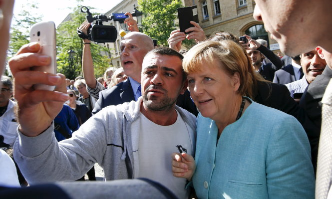 A migrant takes a selfie with German Chancellor Angela Merkel outside a refugee camp near the Federal Office for Migration and Refugees after registration at Berlin's Spandau district, Germany in this September 10, 2015 file photo. Merkel, known for her caution, has taken the high-risk step of opening Germany's doors wide, and implored her European Union partners to follow the example. To match Insight EUROPE-MIGRANTS/GERMANY-INSIGHT REUTERS/Fabrizio Bensch/Files