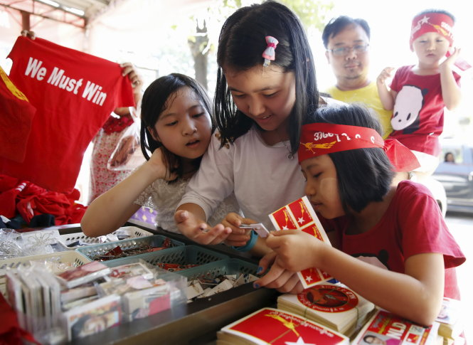 """People buy t-shirts and stickers at the National League for Democracy headquarters ahead of Sunday's general election in Yangon, Myanmar, November 5, 2015. Myanmar opposition leader Aung San Suu Kyi said on Thursday she would be """"above the president"""" if her party wins a historic election on Nov. 8, defying a constitutional ban on becoming head of state herself. The general election is the first since a quasi-civilian government took power in 2011 after nearly 50 years of a military dictatorship, and is widely regarded as a referendum on Myanmar's reform process. REUTERS/Olivia Harris"""