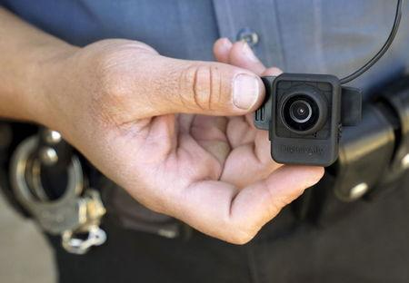 A Colorado Springs police officer poses with a Digital Ally First Vu HD body worn camera outside the police department in Colorado Springs