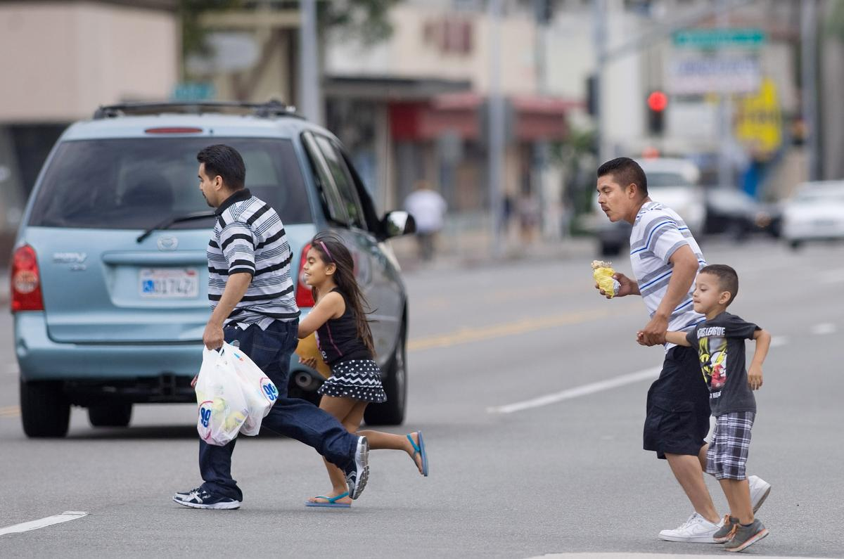 Adults grab ahold of children as they race across Main and 15th Streets in Santa Ana where traffic comes from all directions. There are bus stops on either side of the roads but no crosswalks. A woman was killed several months ago near there. ///ADDITIONAL INFO: - Photo by MINDY SCHAUER, THE ORANGE COUNTY REGISTER -  shot: 101215 deadly.streets.1018 Pedestrians in Santa Ana dodge traffic along Main Street and 15th where there is no nearby crosswalk. A  women died near there earlier this year.