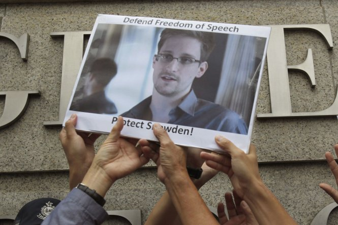 File photo of protesters supporting Snowden hold a photo of him during a demonstration outside the U.S. Consulate in Hong Kong