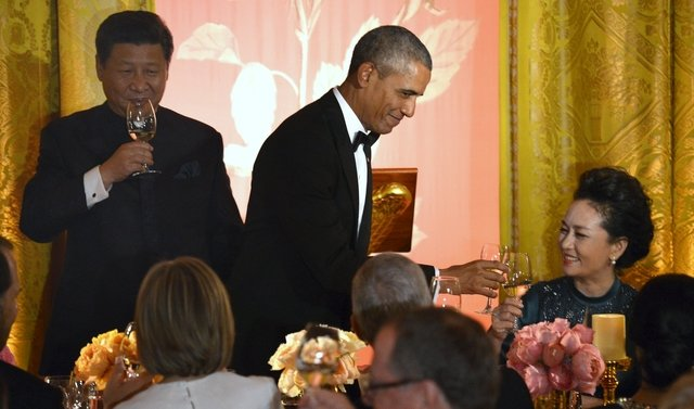"""U.S. President Barack Obama touches his glass in a toast to Chinese President Xi Jinping's spouse Madame Peng Liyuan (R) as Xi (L) joins in, during the State Dinner at the White House, in Washington, September 25, 2015. Obama announced on Friday that he had reached a """"common understanding"""" with Chinese President Xi Jinping on curbing economic cyber espionage, but threatened to impose U.S. sanctions on Chinese hackers who persist with cyber crimes. REUTERS/Mike Theiler"""