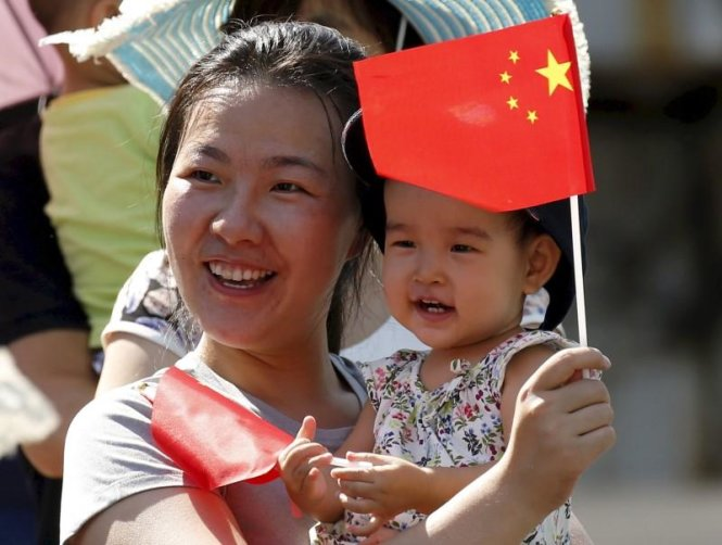 A woman and her baby wait on the street for a military parade marking the 70th anniversary of the end of World War Two, in Beijing, China, in this September 3, 2015 file photo. REUTERS/Kim Kyung-Hoon/Files