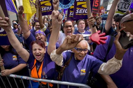 People celebrate the passage of the minimum wage for fast-food workers by the New York State Fast Food Wage Board during a rally in New York July 22, 2015.  REUTERS/Brendan McDermid