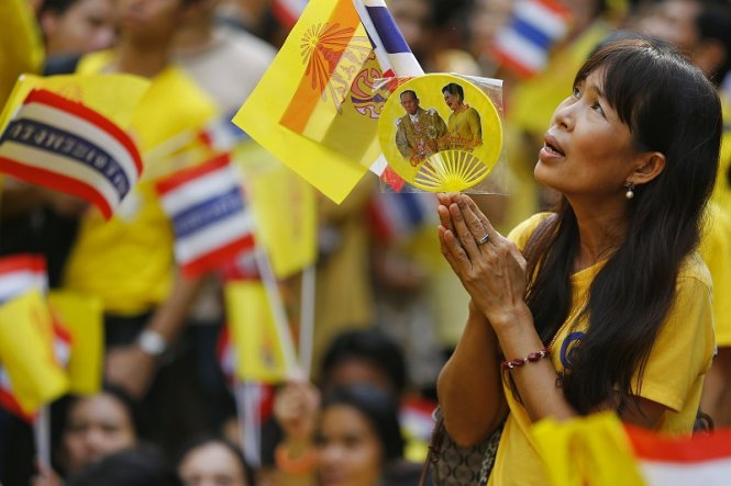 A well-wisher looks toward the building where Thailand's King Bhumibol Adulyadej is residing at Siriraj hospital in Bangkok as people gather there to pray for his health and celebrate his birthday December 5, 2014. Thailand's King Bhumibol Adulyadej cancelled a public appearance on his 87th birthday on Friday on the advice of doctors, disappointing thousands camped outside the hospital hoping for a glimpse of the world's longest-reigning monarch. REUTERS/Damir Sagolj (THAILAND - Tags: ROYALS SOCIETY HEALTH)