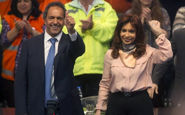 Daniel Scioli (L), Buenos Aires' province governor and presidential candidate for the Victory Front and Argentine President Cristina Fernandez de Kirchner wave to their supporters during a rally marking the Dia del Camino (National Road's Day) in Buenos Aires, October 5, 2015. Opinion polls ahead of the October 25 election have shown Scioli widening his lead over Mauricio Macri and edging closer to the backing needed for a first round win. REUTERS/Agustin Marcarian