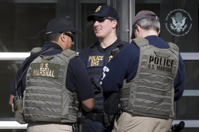 Federal law enforcement officers stand outside the Brooklyn Federal Courthouse in the Brooklyn borough in New York