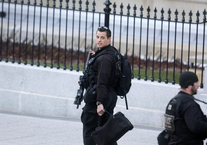 REFILE - CLARIFYING CAPTION U.S. Secret Service agents walk at the White House in Washington, December 18, 2014. The U.S. Secret Service needs strong new leadership from outside the agency and an infusion of agents and uniformed officers - not to mention a better fence - to protect the White House adequately, an independent review panel said on Thursday. REUTERS/Larry Downing (UNITED STATES - Tags: POLITICS CRIME LAW)
